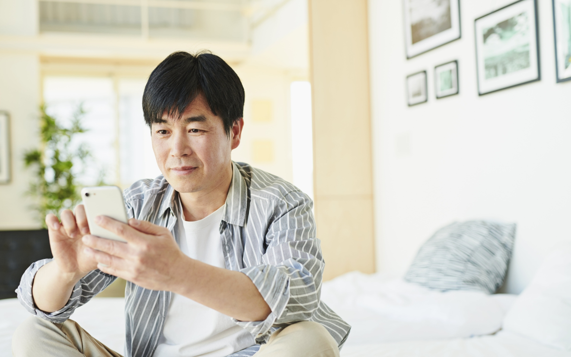 Guest enjoying his hotel room with mobile device